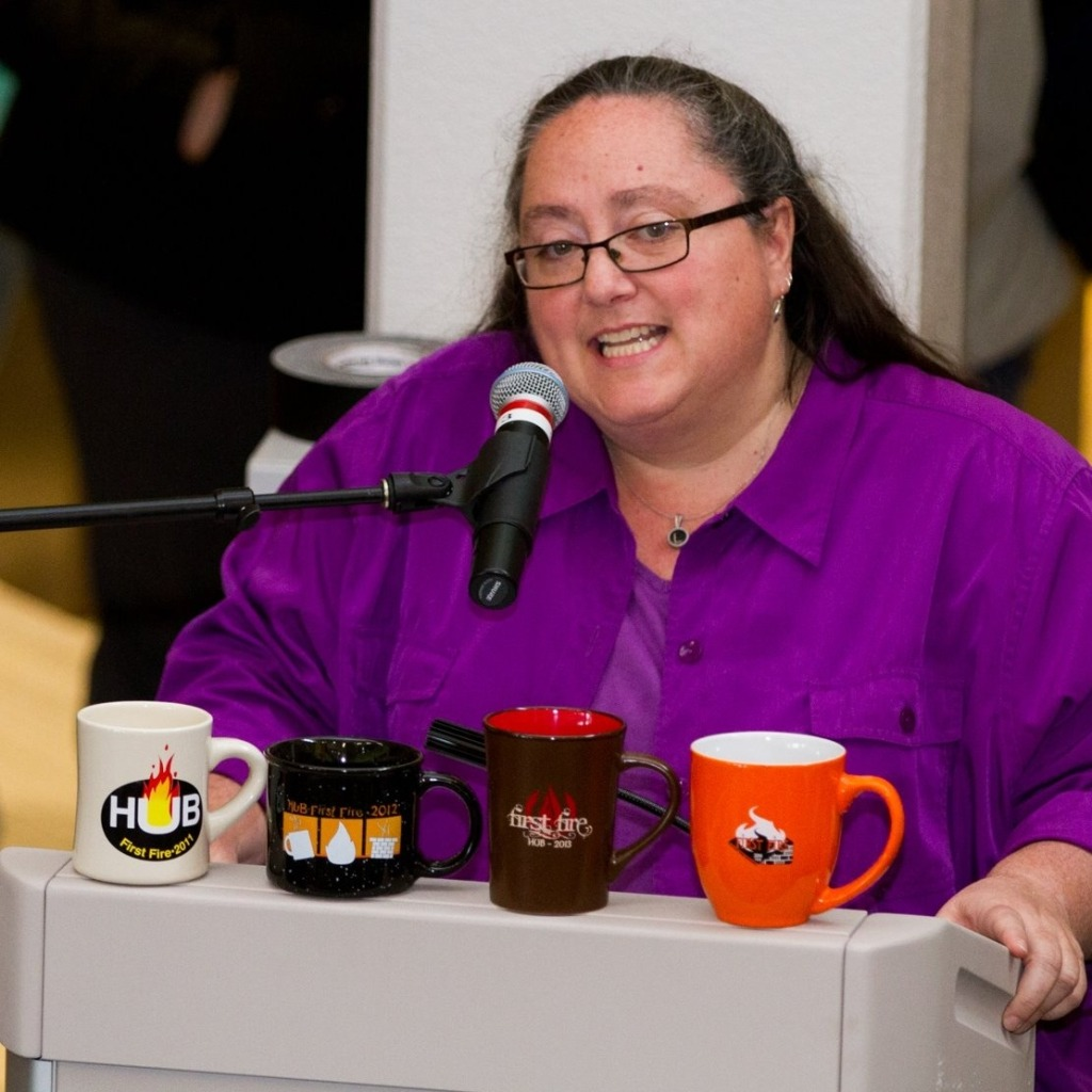 A woman with long brown hair and glasses, wearing a purple shirt, speaks at a podium displaying four coffee mugs